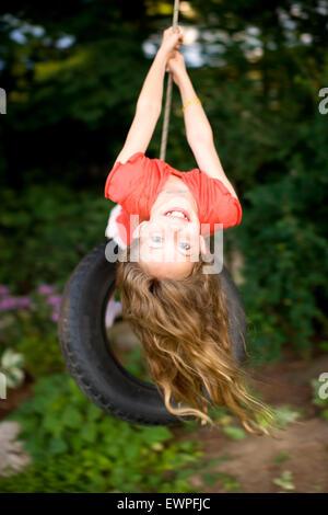 A girl swings on a tire swing in a backyard in Sandpoint, Idaho. - Stock Photo