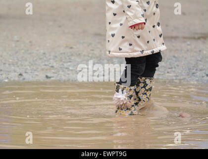 young girl wearing flowered wellington boots walking through muddy puddle - Stock Photo
