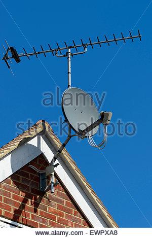 Satellite dish on house roof, Blandford Forum, Dorset England UK - Stock Photo