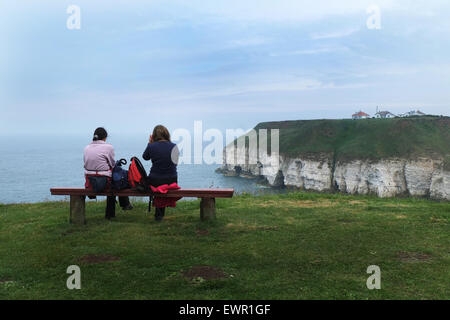 Couple on seat overlooking Thornwick Bay and Flamborough on the Yorkshire coast. - Stock Photo