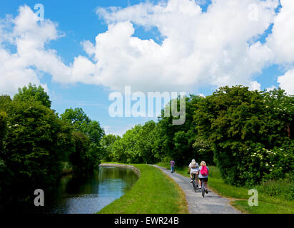 Cyclists on the towpath of the Leeds and Liverpool Canal near Barnoldswick, Lancashire, England UK - Stock Photo