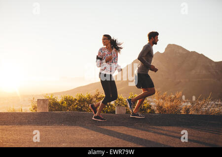 Young couple jogging early in morning, with woman looking back over her shoulder. Young man and woman running outdoors - Stock Photo