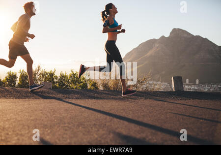 Shot of young man and woman running on country road. Young couple training in nature. - Stock Photo
