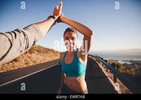 First person view of a man and woman doing a high five. Happy young woman giving high five to man after outdoor - Stock Photo