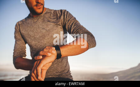 Male athlete checking time while on outdoor training. Young runner checking the time on his sport swatch - Stock Photo