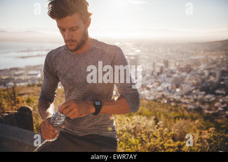Young runner with a water bottle taking a break after hard running training outdoors. Young man relaxing after a - Stock Photo