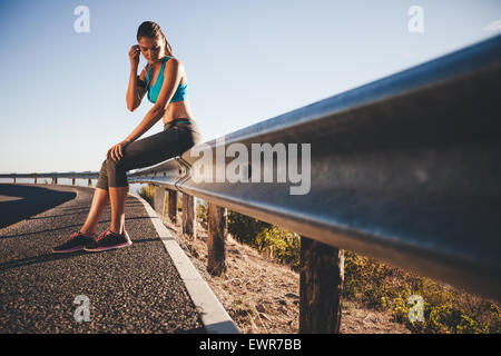 Outdoor shot of young female athlete taking break from running workout, adjusting her earphone. Sports woman sitting - Stock Photo
