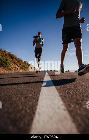 Low angle shot of young woman running on road with man in front. Runners training on country road on summer morning. - Stock Photo