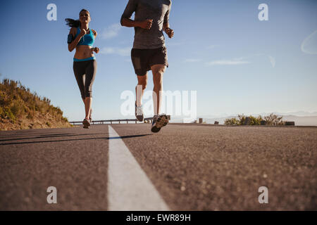 Low angle shot of young woman running on road with man in front on a summer morning. Runners training on country - Stock Photo