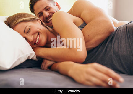 Image of cute young couple in love lying on bed. Man waking up his wife in morning. - Stock Photo