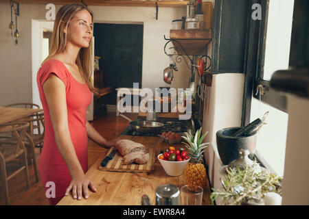 Shot of a pretty young woman standing in her kitchen looking away in thought. Caucasian female looking outside kitchen - Stock Photo