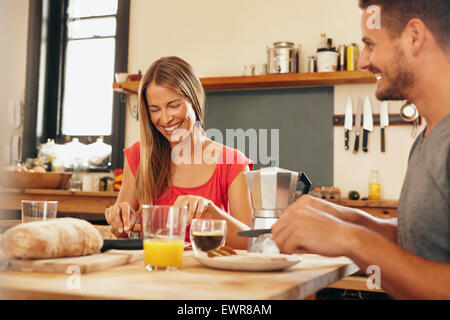 Happy young couple having breakfast together at home. Young woman and man smiling while eating breakfast in kitchen. - Stock Photo