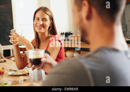 Young couple sitting at breakfast table in morning. Focus on young woman holding glass of fruit juice and man is - Stock Photo