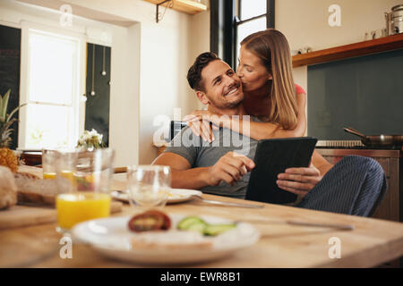 Young man holding a digital tablet while his girlfriend hugs him from behind, giving him a good morning kiss. Young - Stock Photo