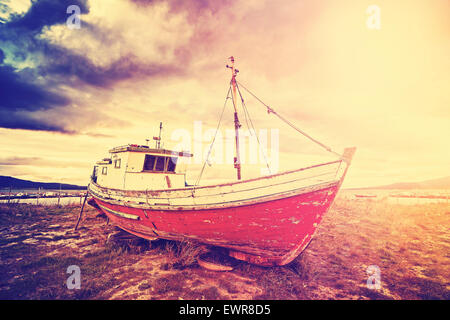 Vintage toned old ship on a beach at dramatic sunset. - Stock Photo