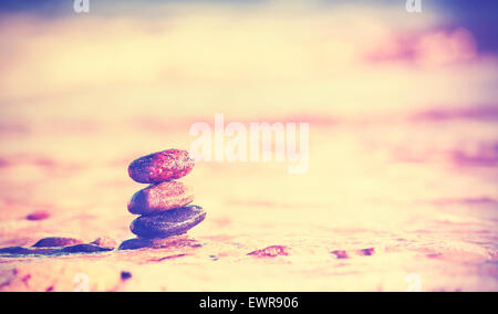 Vintage retro style image of stones on beach, Zen spa concept background. - Stock Photo