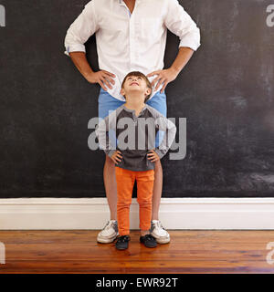 Indoor shot of little boy looking at his father while standing in front with hands on waist. - Stock Photo