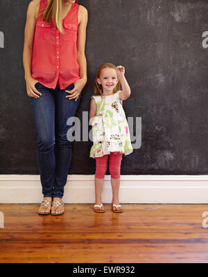 Image of cute little girl standing with her mother at home. Mother and daughter standing together against a black - Stock Photo