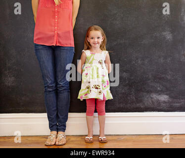 Little girl with sweet smile standing with her mother. Mother is cropped in the picture with focus on little girl - Stock Photo
