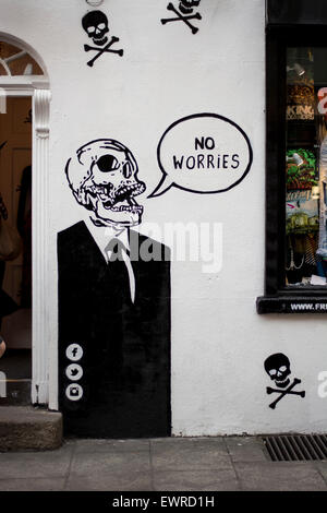 Graffiti artwork of a Skull in a suit with speech bubble 'no Worries' on a wall on a wall in Temple bar, Dublin - Stock Photo