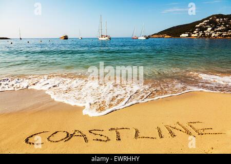 Coastline word in sand written on beach Spanish fun resort seas coast coastlines holidays vacations trips trip getaway - Stock Photo