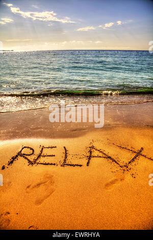 Relax in sand word written on beach coast chill holiday getaway sea coastline Ibiza Spain Spanish Santa Eulalia - Stock Photo