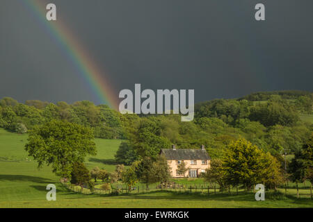 Rainbow and black skies,sky during a heavy rain shower over a rural house,residence near Llanfair Caereinion,Powys,Wales,U.K. - Stock Photo