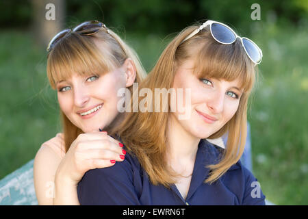 Two pretty women having fun at the summer park. Twins girls are posing looking to the camera - Stock Photo