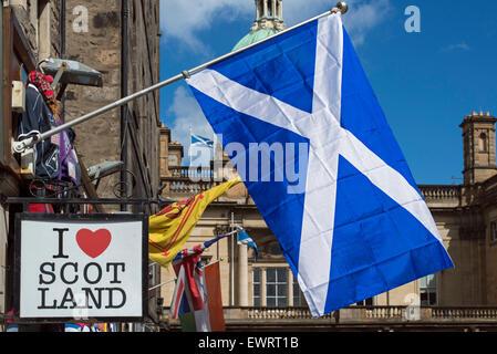 The Scottish Saltire flying outside a tourist souvenir shop in Edinburgh's Old Town. - Stock Photo