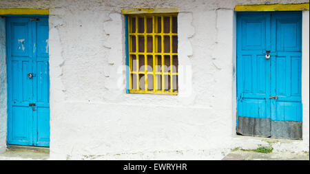 Mediterranean style architecture with yellow metal bars covering window and light blue doors on white house - Stock Photo