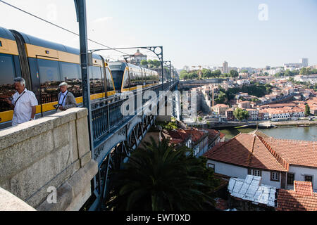 Tourists on top of Dom Luis I Bridge, which at upper level is both a walkway and a metro train line, with view of - Stock Photo