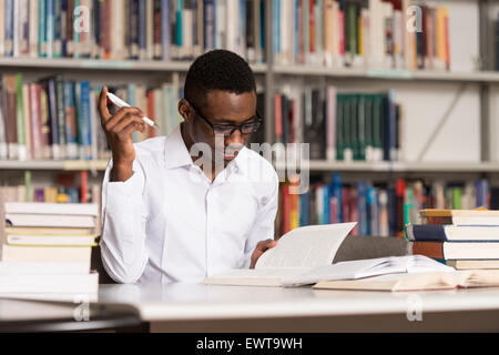 ... Portrait Of African Clever Student With Open Book Reading It In College  Library   Shallow Depth