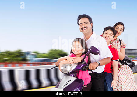 indian Parents and kids road Riding Scooty - Stock Photo