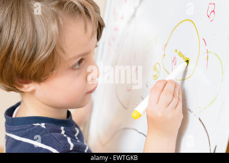 Cute boy drawing at kindergarten on a white board - Stock Photo