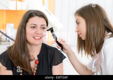 Otolaryngologist examining a woman ear in a clinic - Stock Photo
