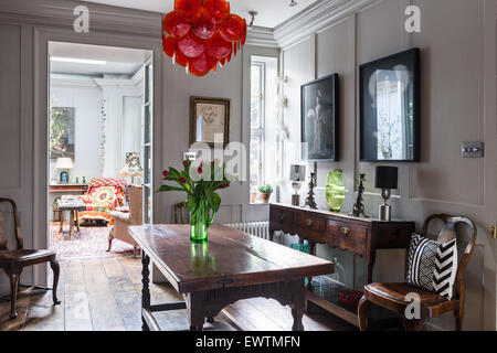 Pair of photographs by Chan-Hyo Bae above oak dresser in panelled dining room with 1960's red glass disc chandelier - Stock Photo