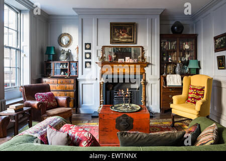 Red chinese chest in living room with Khotan rug from Turkestan, French leather armchair and walnut display cabinets - Stock Photo