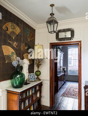 Marble-topped bookshelf in hallway with antique fan artwork and reclaimed wooden flooring - Stock Photo