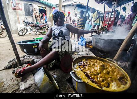 A woman cooks a stew in West Point, Monrovia, Liberia - Stock Photo