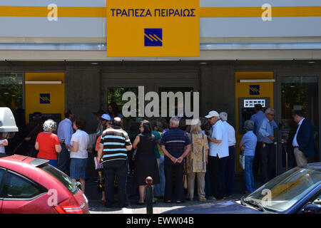 Crowd of people queue at Piraeus bank branch open only for pensioners without ATM access. Capital controls in Greece. - Stock Photo