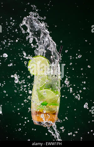 Mojito drink splashing out with dark background - Stock Photo