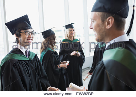 College graduates in cap and gown talking - Stock Photo