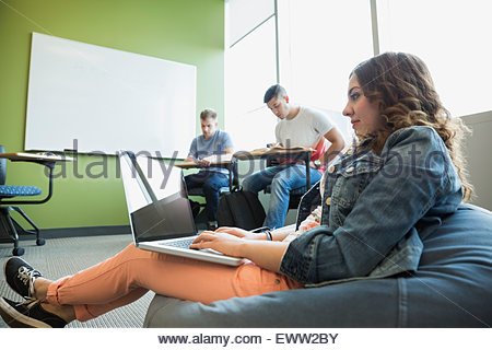 College student using laptop on bean bag chair - Stock Photo