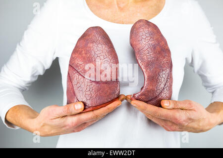 Woman showing models of two lungs in front of chest to symbolize breathing for education - Stock Photo