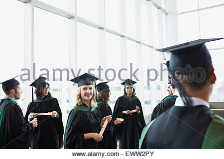 Portrait smiling college graduate in cap and gown - Stock Photo