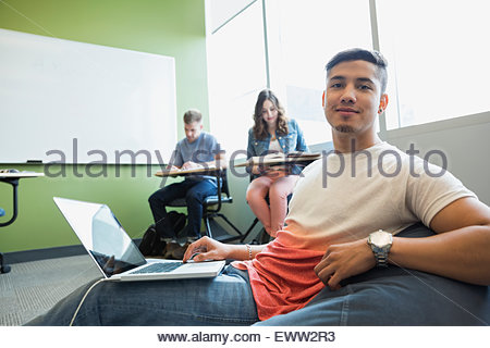 Portrait college student with laptop bean bag chair - Stock Photo