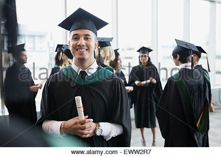 Portrait confident college graduate cap and gown diploma - Stock Photo