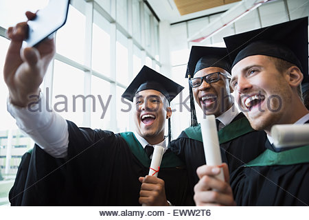 Enthusiastic college graduates cap and gown taking selfie - Stock Photo