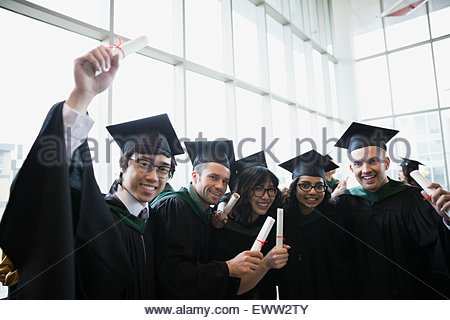 Portrait enthusiastic college graduates in cap and gown - Stock Photo