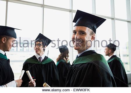 Portrait confident college graduate in cap and gown - Stock Photo